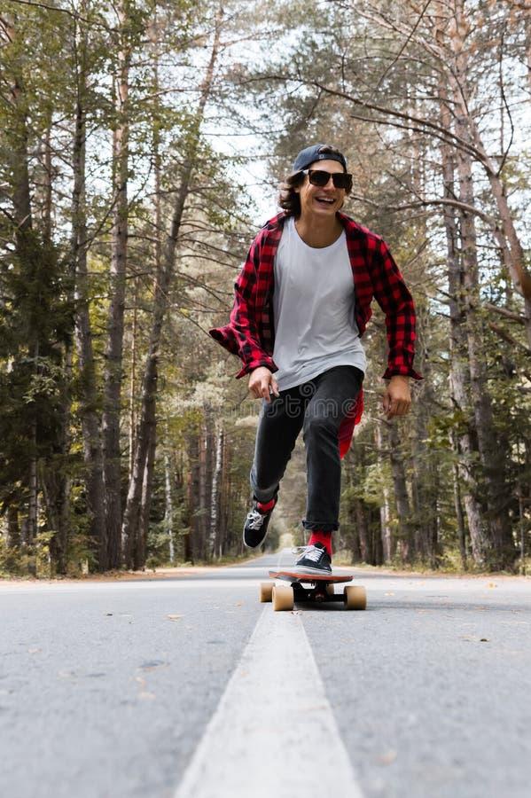 Ein junger lachender Hippie in einer Kappe und in einem karierten Hemd reitet sein longboard auf eine Landstraße im Wald lizenzfreies stockbild