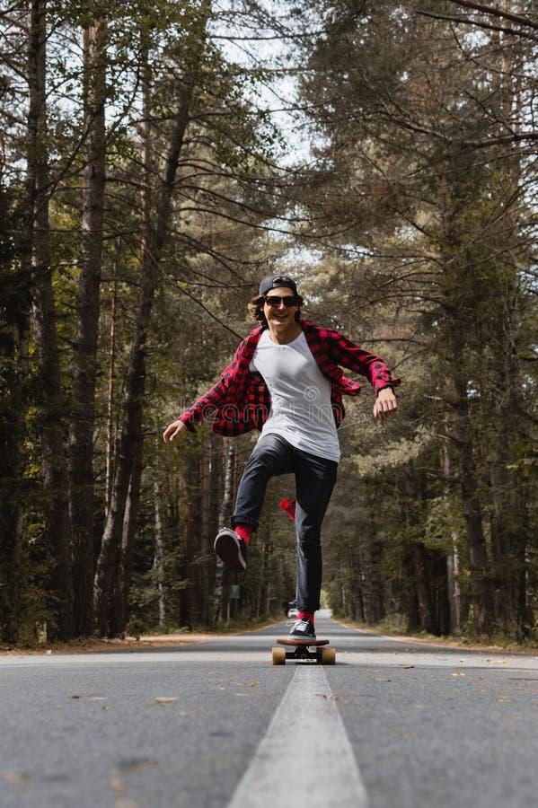 Ein junger lachender Hippie in einer Kappe und in einem karierten Hemd reitet sein longboard auf eine Landstraße im Wald stockbild