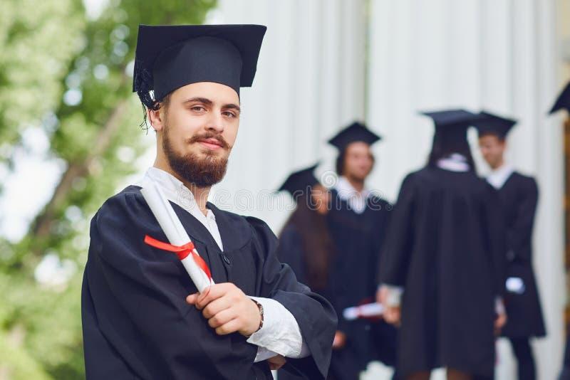 Ein junger männlicher Absolvent vor dem hintergrund der Hochschulabsolvent stockbild
