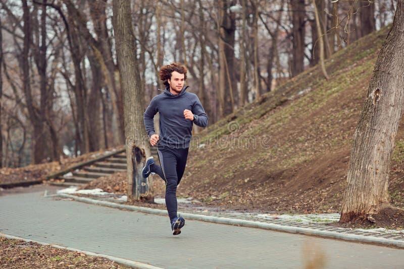Ein junger männlicher Läufer läuft in den Park lizenzfreie stockfotos