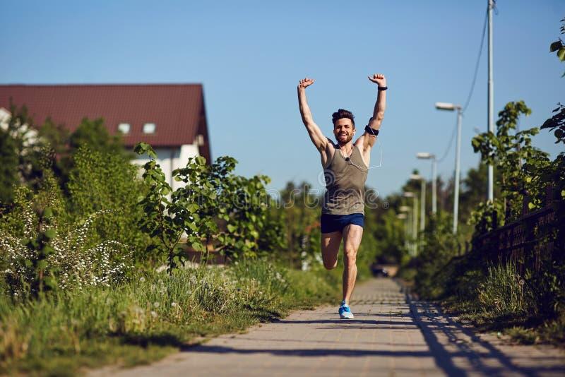 Ein junger männlicher Läufer läuft mit seinen Armen, die in den Park angehoben werden lizenzfreies stockbild