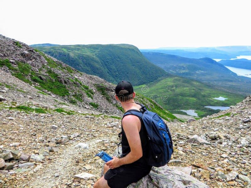 Ein junger männlicher Wanderer, der die großartigen Ansichten von auf Gros Morne Mountain in Gros Morne National Park bewundert lizenzfreies stockfoto