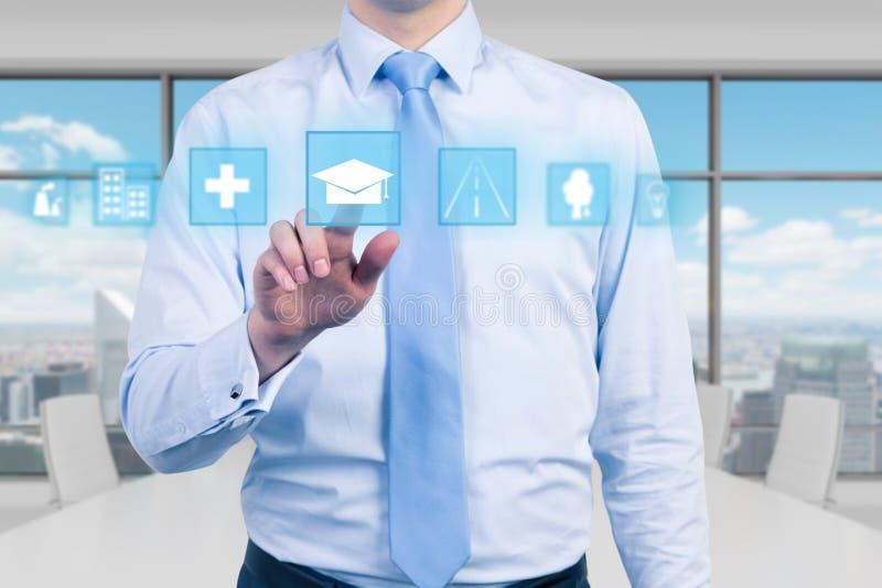 Ein junger Manager im modernen panoramischen Büro drückt die pädagogische Ikone Ein Konzept der Geschäftsbildung stockfoto