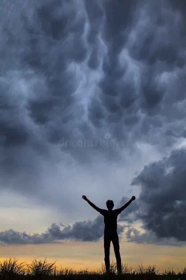 Ein junger Mann allein, der seine Hände oben gegen einen drastischen Himmel an der Dämmerung hält stockbild