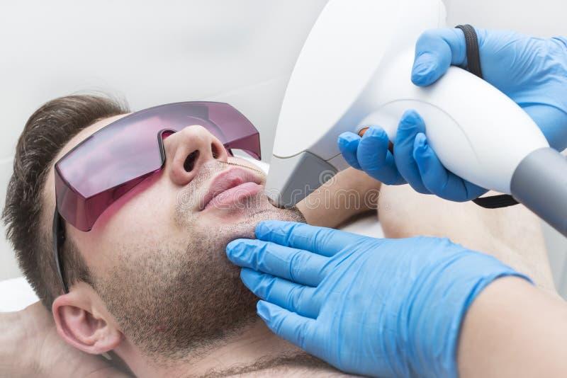 Ein junger Mann auf einem Verfahren des Laser-Haarabbaus in den Salon lizenzfreie stockbilder