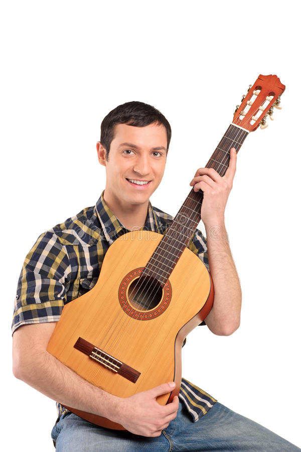 Ein junger Mann, der Akustikgitarre spielt lizenzfreie stockbilder