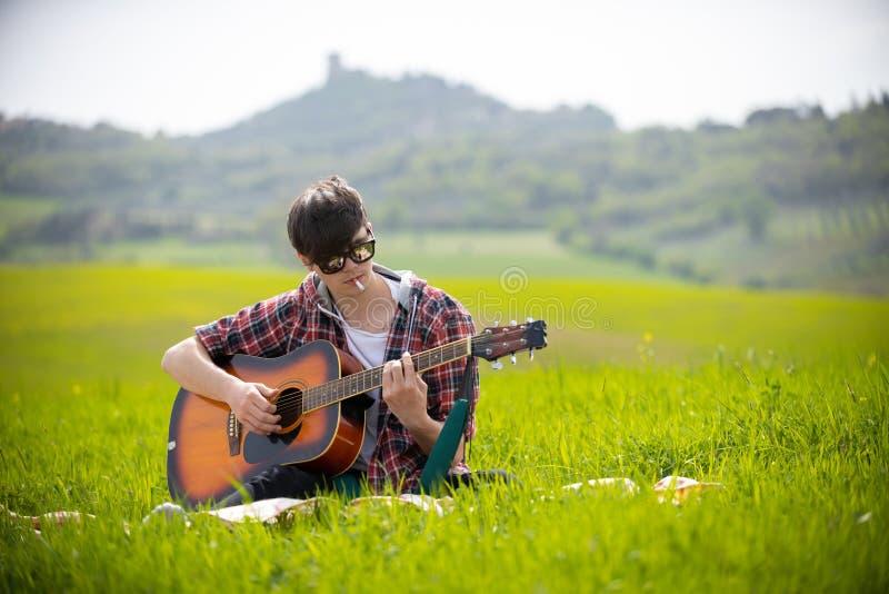 Ein junger Mann, der auf einer hellgrünen Wiese spielt Gitarre und raucht Zigarette sitzt stockfoto