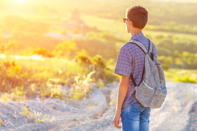 Ein junger Mann, der auf der Straße mit einem Rucksack weg betrachtet der Sonne steht lizenzfreie stockfotos