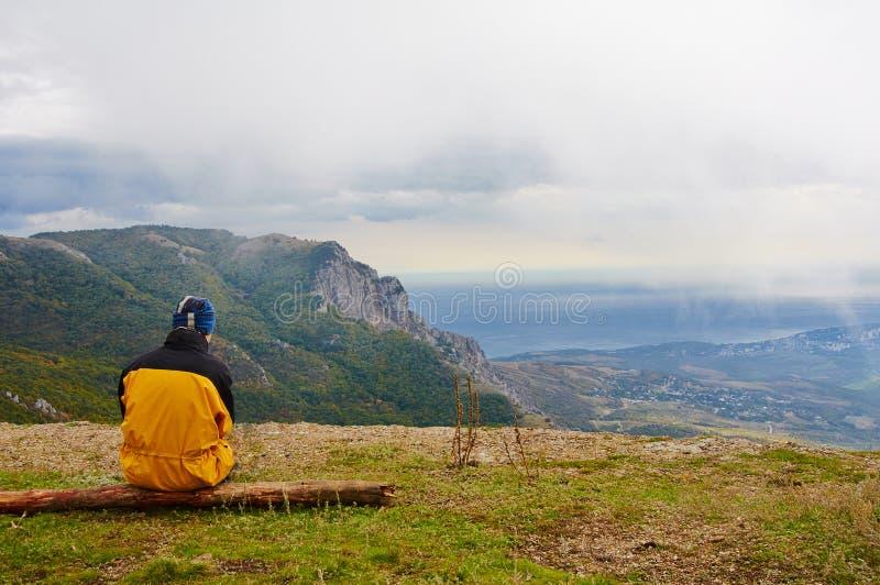 Ein junger Mann, der in den Bergen, er fehlt ihm kalt einsam steht, wartet er auf jemand stockfoto