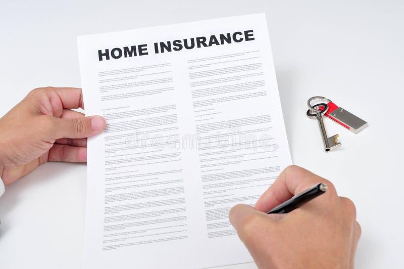 Ein junger Mann, der eine Hausversicherungspolitik unterzeichnet lizenzfreie stockfotografie