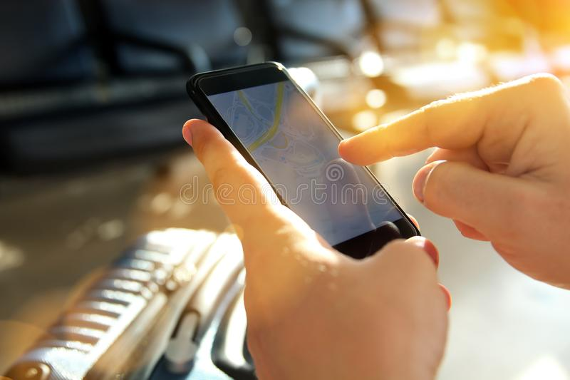 Ein junger Mann, der eine Karte an seinem Handy auf den Flughafen betrachtet lizenzfreie stockfotografie