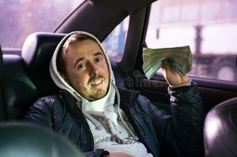Ein junger Mann, der in einem Auto mit einem großen Bündel Geld sitzt stockbild
