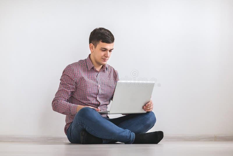 Ein junger Mann, der an einem Laptop arbeitet stockfotografie