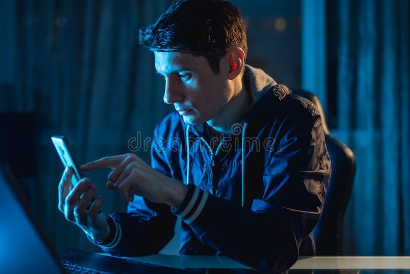 Ein junger Mann, der an einem Laptop nachts arbeitet Designer oder Systemverwalter blieben spät bei der Arbeit lizenzfreie stockfotografie