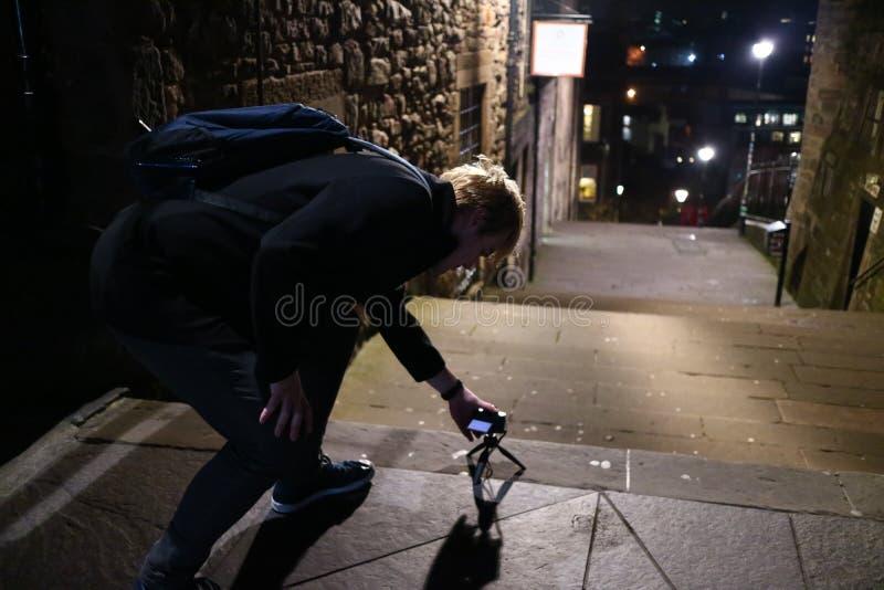Ein junger Mann, der Fotos auf den Straßen von Edinburgh nachts macht lizenzfreie stockfotografie