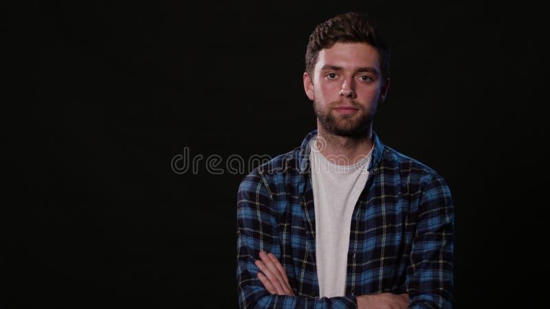 Ein junger Mann, der gegen einen schwarzen Hintergrund mimicing ist lizenzfreies stockbild