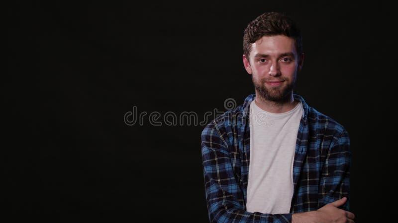 Ein junger Mann, der gegen einen schwarzen Hintergrund mimicing ist stockfotos
