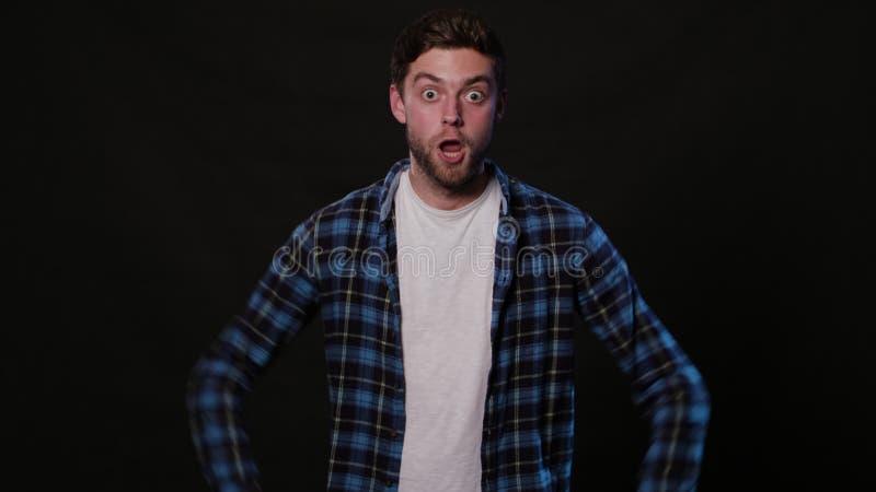 Ein junger Mann, der gegen einen schwarzen Hintergrund mimicing ist lizenzfreie stockbilder