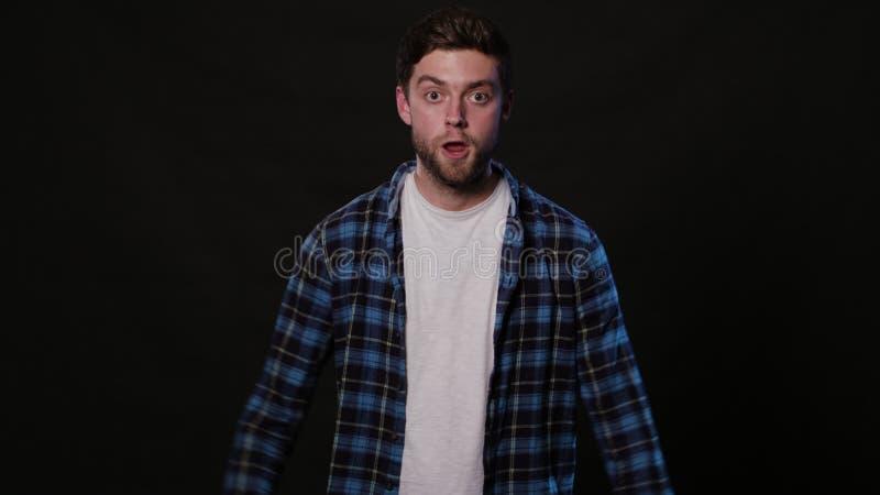 Ein junger Mann, der gegen einen schwarzen Hintergrund mimicing ist lizenzfreie stockfotos
