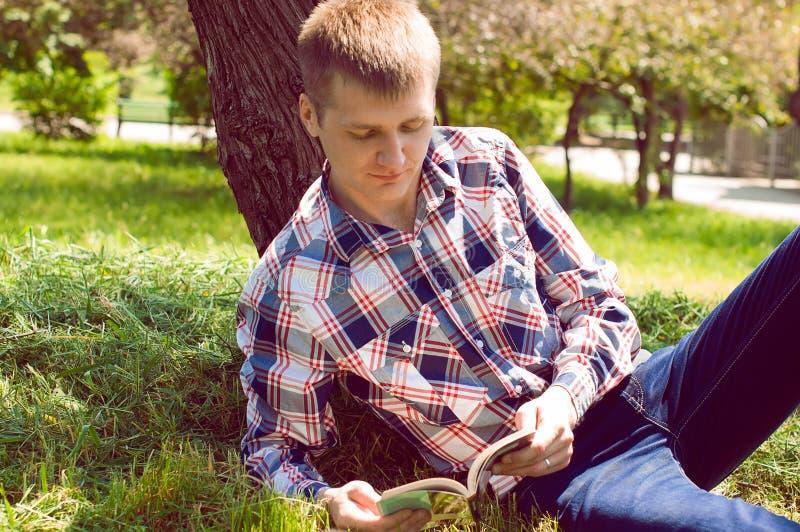 Ein junger Mann, der unter einem Baum, ein Buch lesend sich entspannt lizenzfreie stockbilder