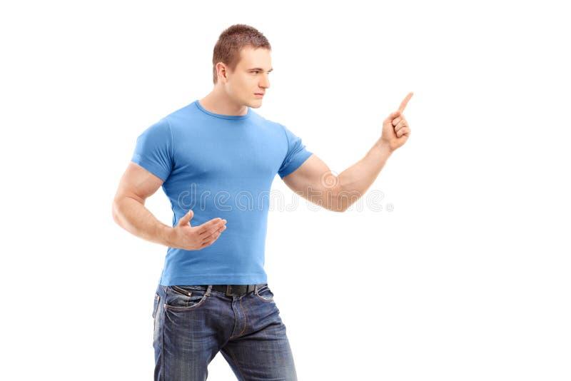 Ein junger Mann des Ärgers, der mit dem Finger und dem Bedrohen zeigt stockfoto