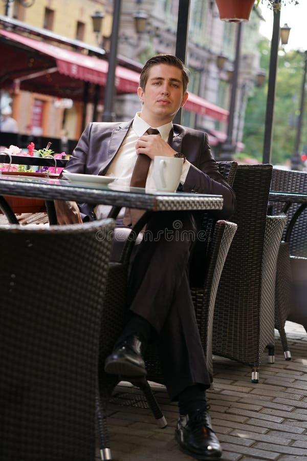 Ein junger Mann in einem Anzug berührt und richtet seine Bindung gerade lizenzfreies stockbild