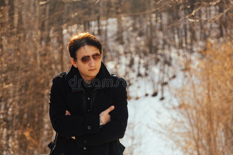 Ein junger Mann in einem Mantel und in der Sonnenbrille in der Natur lizenzfreies stockbild