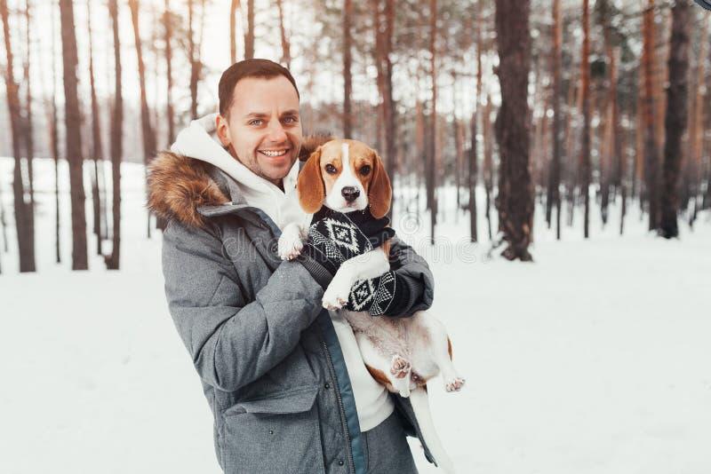 Ein junger Mann in einem Wald des verschneiten Winters hält einen Hunderasse Spürhund lizenzfreie stockfotos