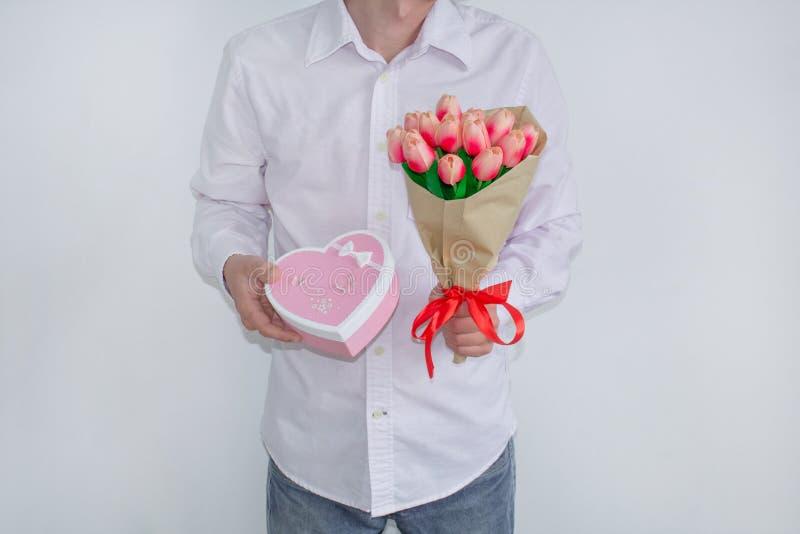 Ein junger Mann in einem weißen Hemd und in den Jeans, einen Blumenstrauß von Tulpen und von Herz-förmigen Geschenkbox, auf einem stockbild