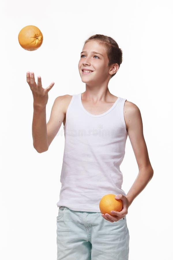 Ein junger Mann in einem weißen Hemd wirft eine Orange und der andere hält in der Hand lizenzfreies stockfoto