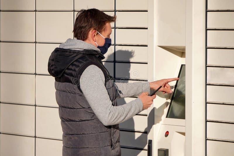 Ein junger Mann in einer blauen Maske holt ein Paket bei Boxes für Pakete ein Kontaktlose oder unberührte Lieferung von Waren und lizenzfreies stockfoto