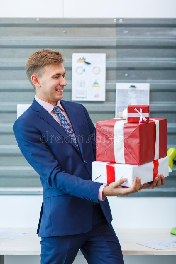 Ein junger Mann im Büro empfängt ein Geschenk stockfotografie