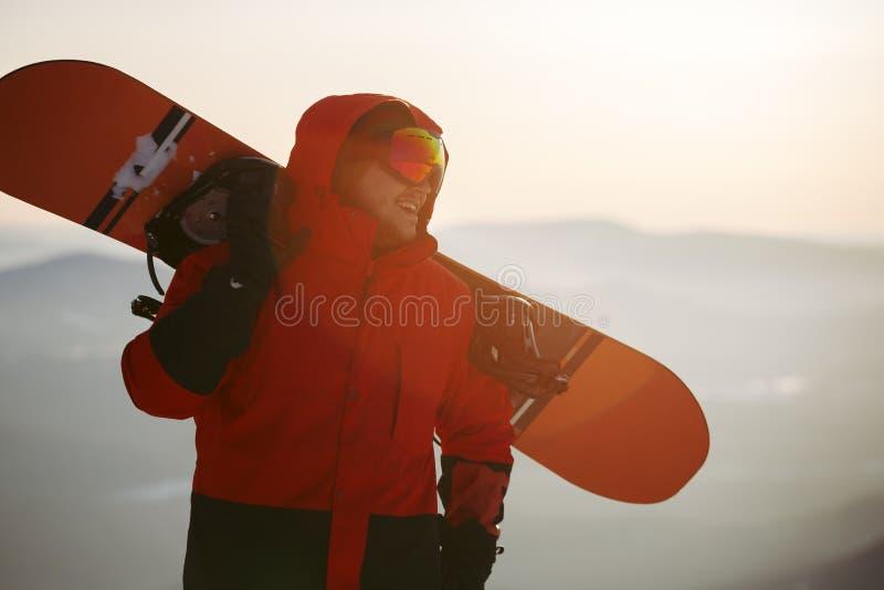 Ein junger Mann im Hintergrund des SonnenuntergangHimmelshimmels mit Snowboard stockbilder