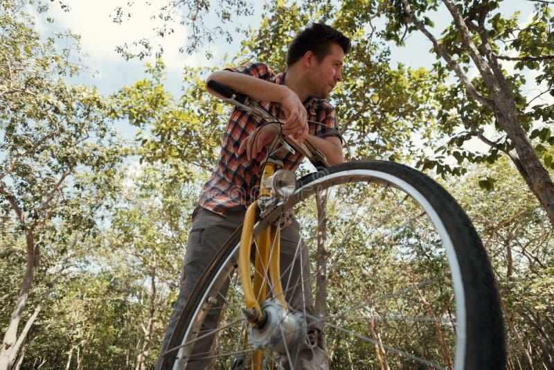 Ein junger Mann ist vom Fahren Fahrrads müde Es ` s heißes äußeres und er möchte trinken stockbild