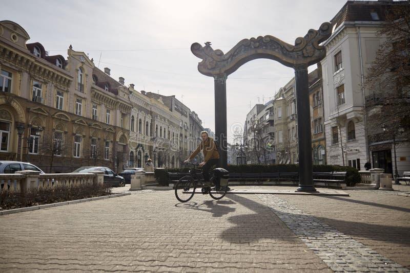 Ein junger Mann, 20-29 Jahre alt, Reitenfahrrad auf einem alten Stadtplatz Alte europäische Architektur, Stadtgebiet lizenzfreie stockfotografie
