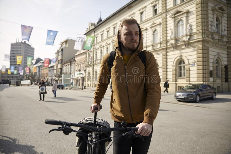Ein junger Mann, 20-29 Jahre alt, tragende Jacke und Hoodie, sein Fahrrad in der Stadt drückend, Fußgängerbereichsstadtgebiet lizenzfreie stockfotografie