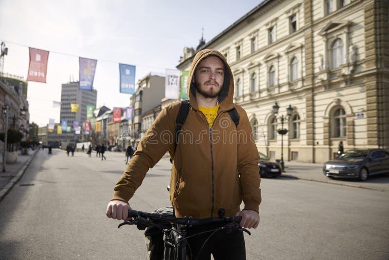 Ein junger Mann, 20-29 Jahre alt, tragende Jacke und Hoodie, sein Fahrrad in der Stadt drückend, Fußgängerbereichsstadtgebiet stockfotografie
