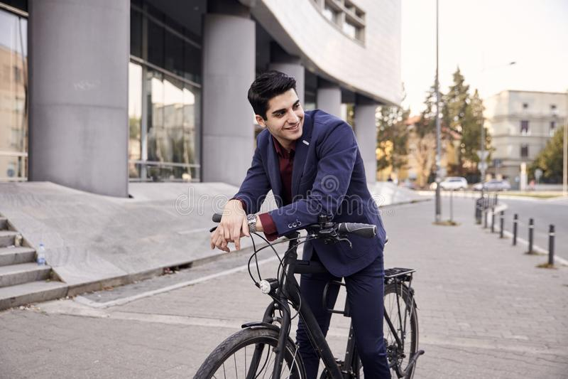 Ein junger Mann, 20-29 Jahre alt, tragender Anzug, seitlich schauend und lächeln Aufstellung auf dem fantastischen Stadtfahrrad,  stockbild