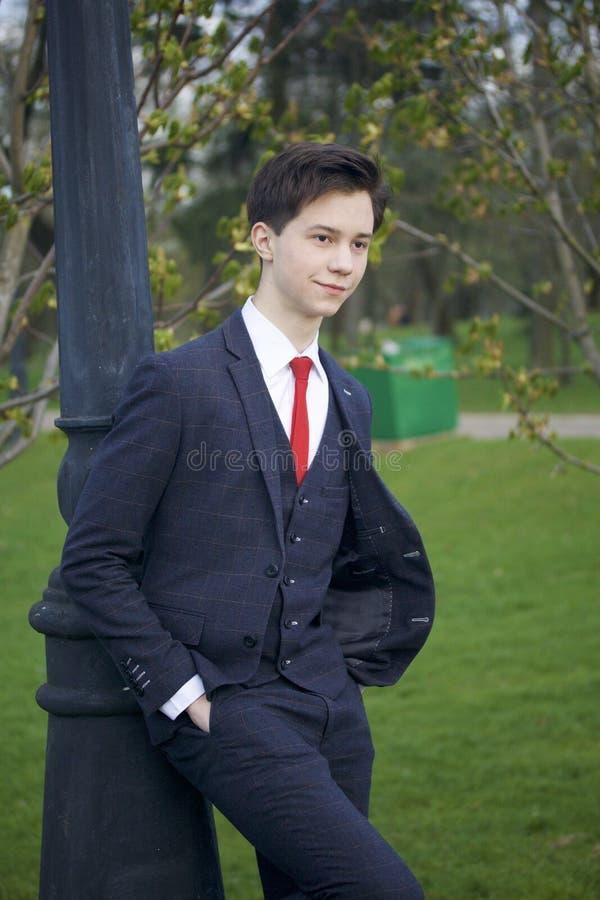 Ein junger Mann, ein Jugendlicher, in einer klassischen Klage Bauen auf eine Weinleselaterne im Park Setzen Sie Ihre Hände in Ihr stockbild