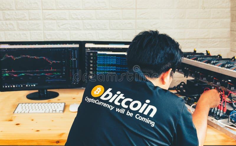 Ein junger Mann konfiguriert Hardware für bitcoin Bergbau stockfoto
