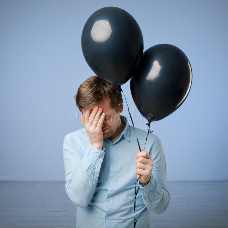 Ein junger Mann leidet unter einem Kater nach einer Partei Er hält in seinen Handschwarzen Ballonen lizenzfreie stockfotografie