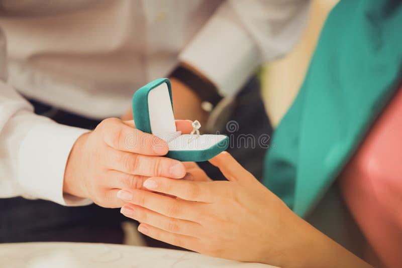 Ein junger Mann macht seiner Freundin einen Heiratantrag und überrascht sie mit einem schönen Verlobungsring stockfotografie