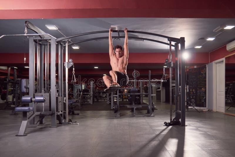 Ein junger Mann, Mehrplatzturnhallen-Maschinen-ABS trainieren, dunkle Turnhalle stockfotos