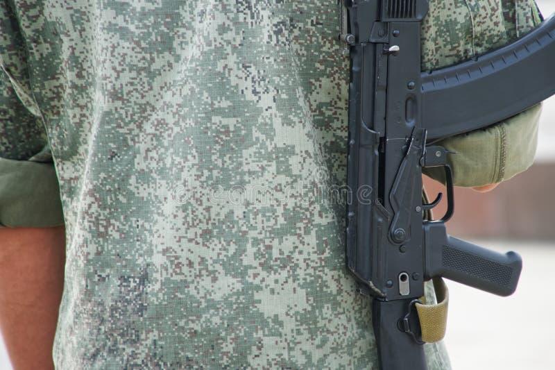 Ein junger Mann mit einem Gewehr hinter ihm geht die Straße hinunter Patrouille oder Sicherheit Bundesfeuerwaffen genehmigen Akel stockfotografie