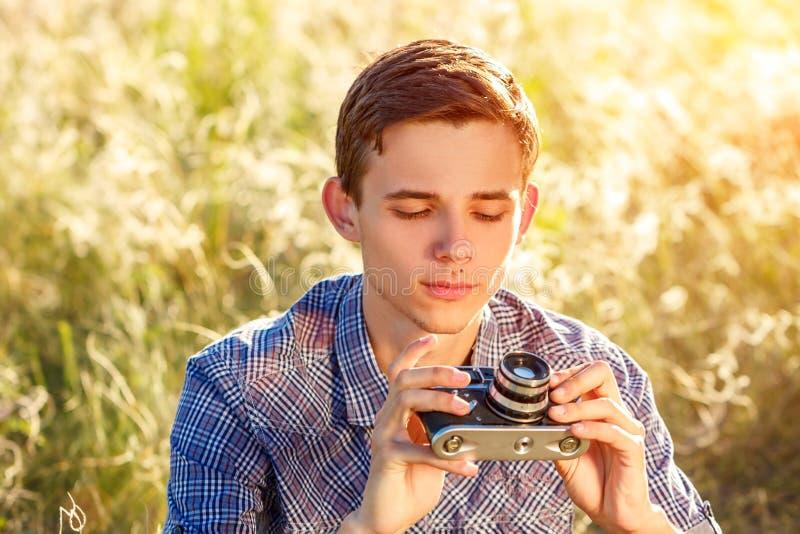 Ein junger Mann mit einer Kamera, die Fotos der Sonnenstrahlen des natürlichen Hintergrundes abgetönt macht lizenzfreie stockfotografie