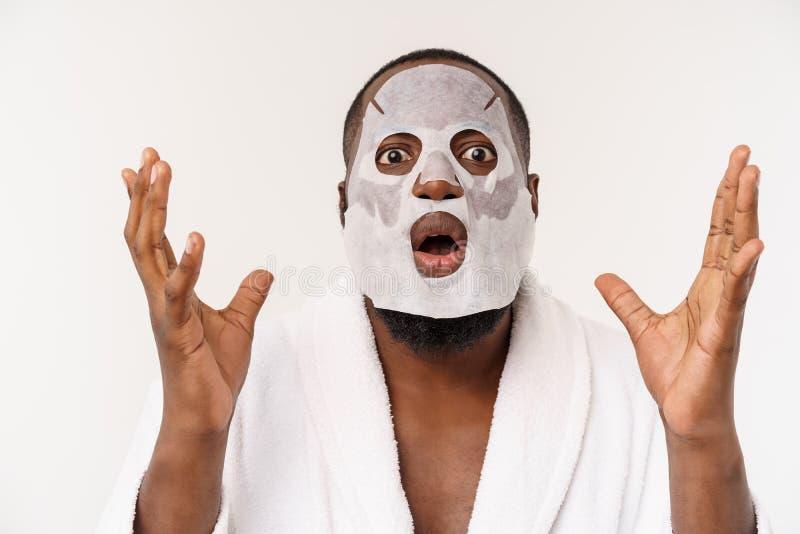 Ein junger Mann mit Papiermaske auf dem Gesicht, das mit einem offenen Mund, lokalisiert auf einem weißen Hintergrund entsetzt sc lizenzfreie stockfotografie