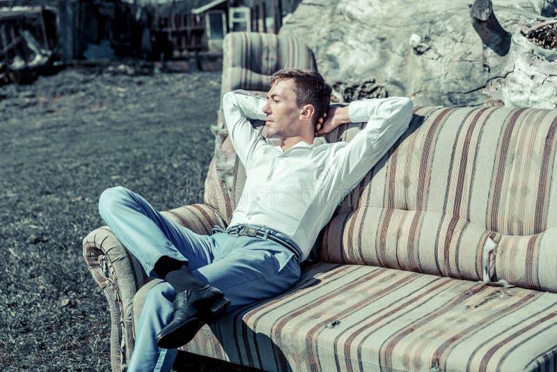 Ein junger Mann sitzt auf der Couch in den Straßenhänden hinter seinem Kopf stockfotografie