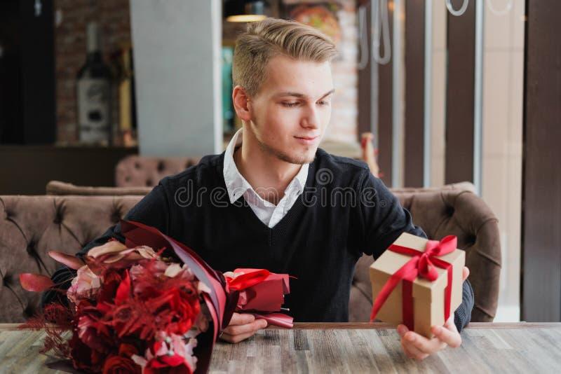 Ein junger Mann sitzt in einem Restaurant und wartet auf eine Sitzung mit einer Freundin, Freundin oder Frau Blumen und ein Gesch stockbild