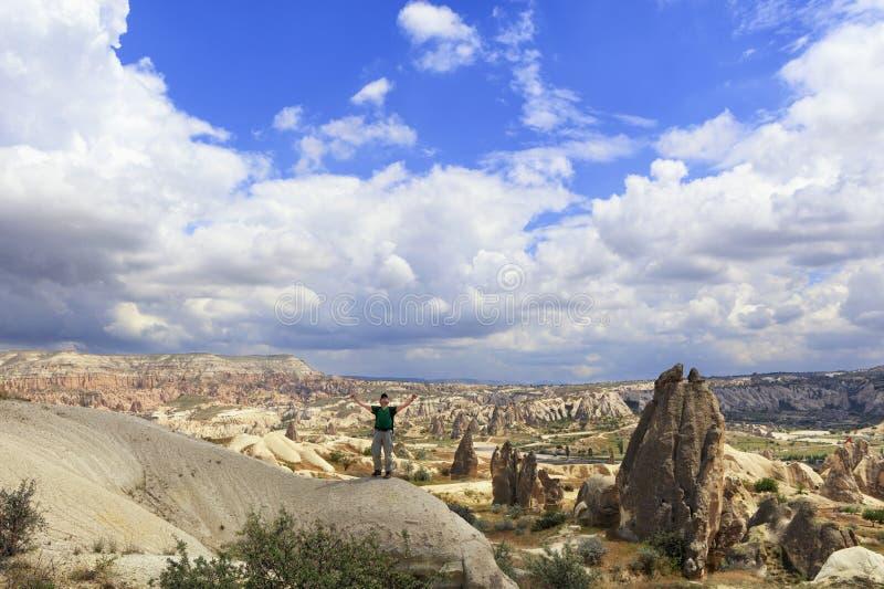 Ein junger Mann steht auf einen Hügel und betrachtet oben einem bewölkten blauen Himmel in Cappadocia stockbilder