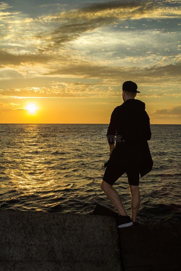 Ein junger Mann steht das Meer bereit und betrachtet den Sonnenuntergang lizenzfreie stockbilder